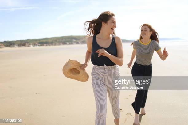 two young women enjoying on the beach - female friendship stock pictures, royalty-free photos & images