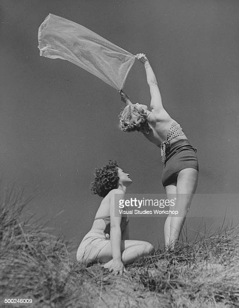 Two young women enjoying the sea breeze on the sand dunes Bude Cornwall England early to mid 20th century