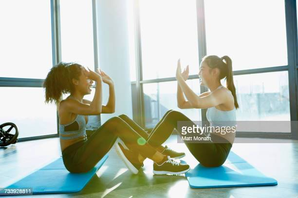 Two young women exercising in gym, doing sit-ups