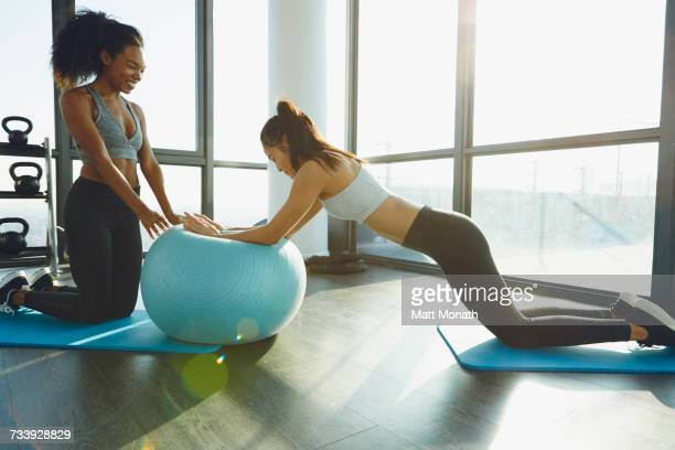 two young women exercising in gym, using inflatable exercise ball - fitness ball stock pictures, royalty-free photos & images