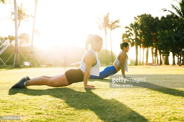 Two young women exercising outdoors, stretching, South Point Park, Miami Beach, Florida, USA