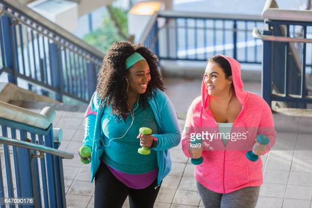 two young women exercising, powerwalking up stairs - chubby stock photos and pictures