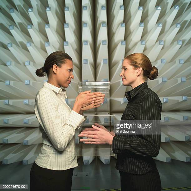 Two young women face to face holding perspex cubes