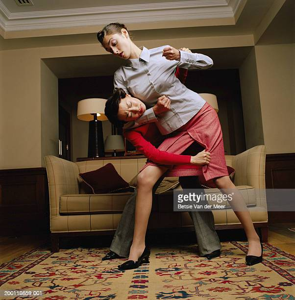 Two young women fighting in living room, low angle view