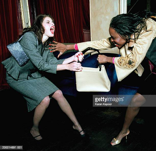 Two young women fighting over handbag