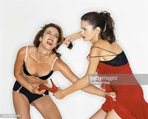 Two young women fighting over high heeled shoe