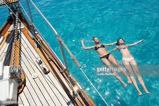 Two young women floating in sea by sailboat, elevated view