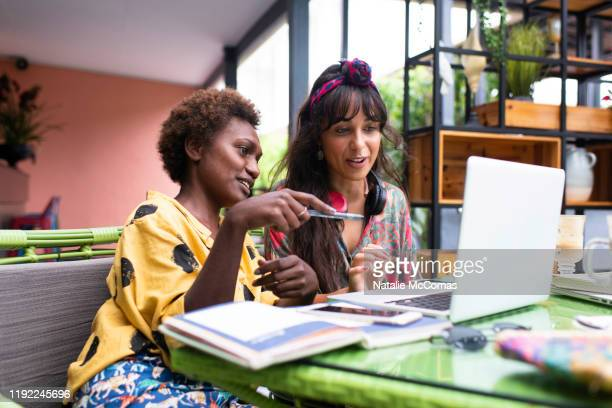 two young women friends at a cafe working on laptop - pacific islands stock pictures, royalty-free photos & images