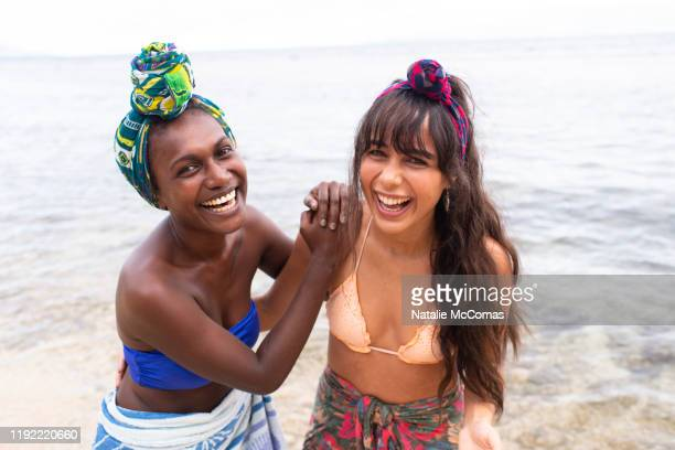 two young women friends at the beach laughing together - showus foto e immagini stock