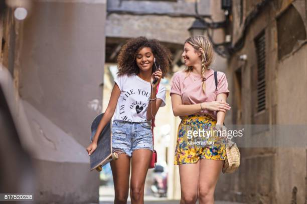 Two young women friends having fun sharing music in the street