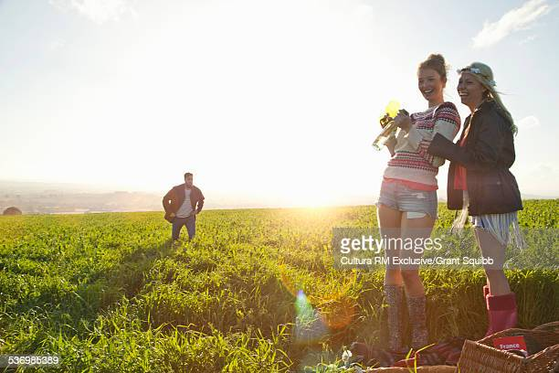 Two young women friends picnicing and laughing in rural field watched by young man
