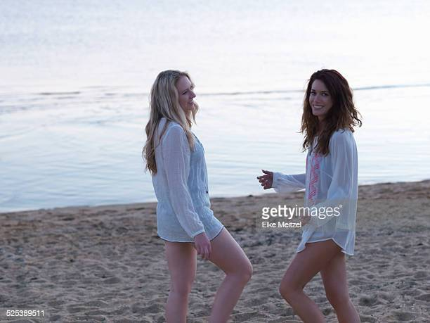 Two young women friends standing chatting on beach at dusk, Williamstown, Melbourne, Australia