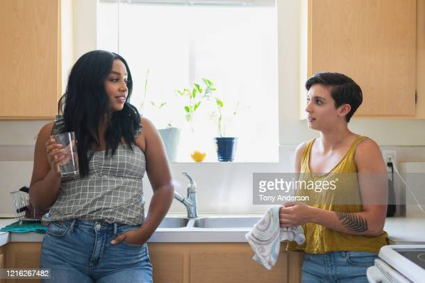 two young women friends talking together in kitchen - bisexuality fotografías e imágenes de stock