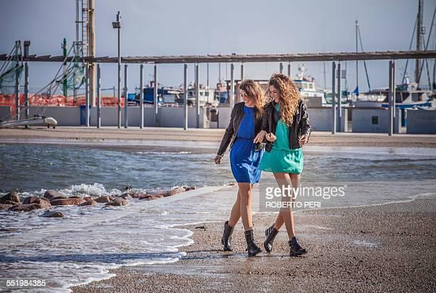 Two young women friends walking on beach