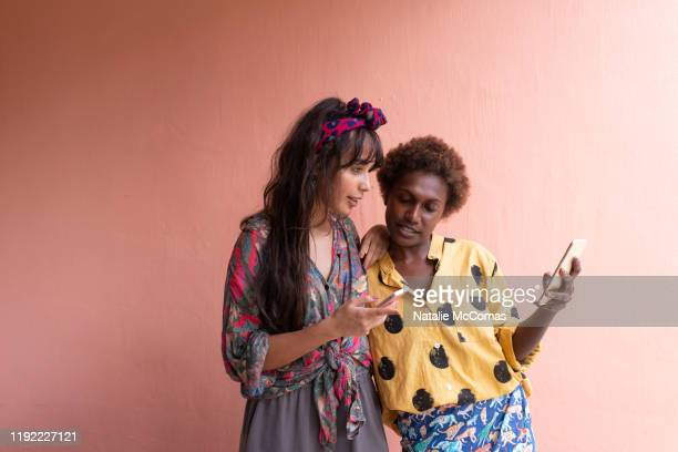 two young women friends with mobile phones in front of pink wall - showus stock pictures, royalty-free photos & images