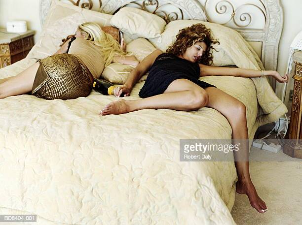 two young women, fully clothed, asleep on bed - drunk woman stock pictures, royalty-free photos & images