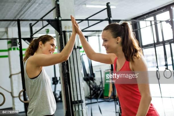 Dos mujeres jóvenes dando cinco alta en el gimnasio