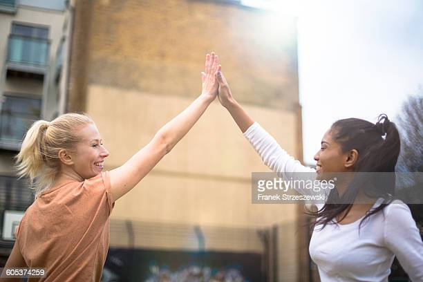 Two young women giving high five, outdoors