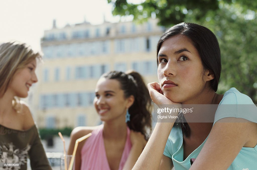 Two Young Women Gossiping About a Woman With Her Hand on Her Chin in the Foreground : Stock Photo