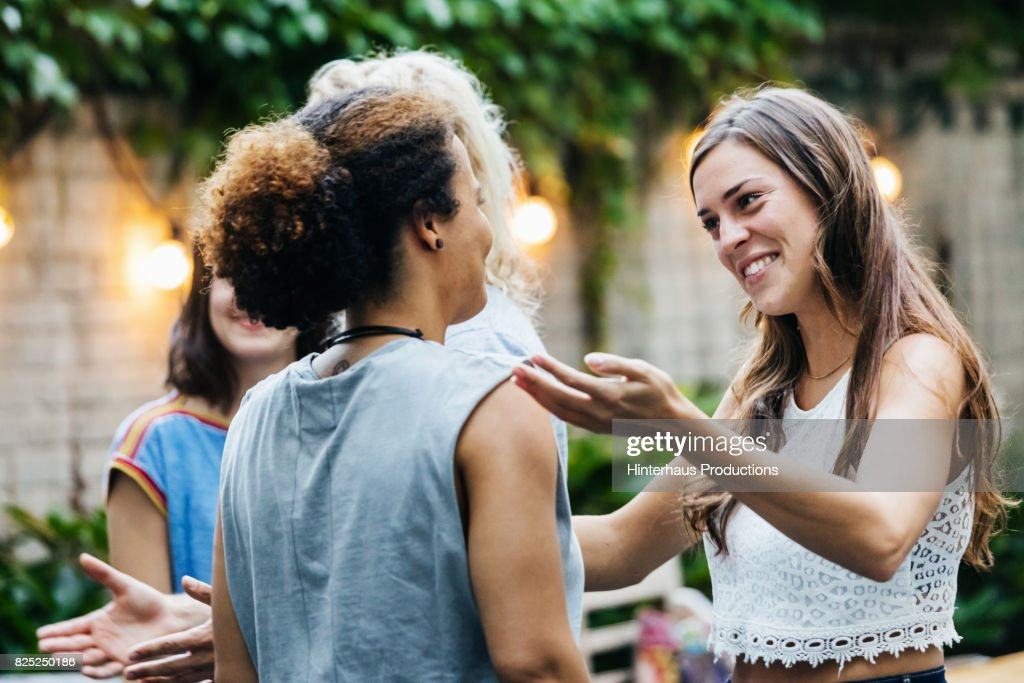 Two Young Women Greeting Each Other During Barbecue Meetup : Stock-Foto