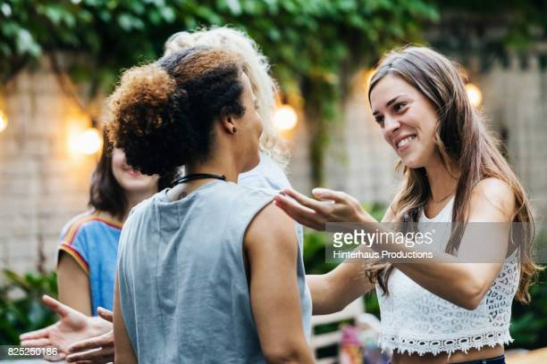 two young women greeting each other during barbecue meetup - greeting stock-fotos und bilder