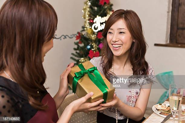 Two Young Women Handing Christmas Present