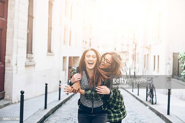two young women having fun and embracing on street - close to stock pictures, royalty-free photos & images