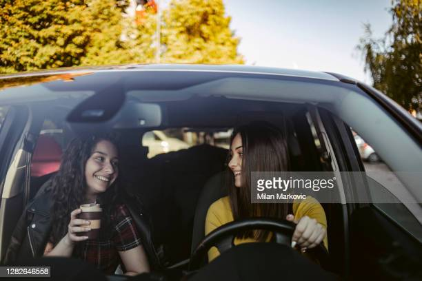 two young women having fun driving along a street - two young female students drive a car and enjoy the journey with relief - singing stock pictures, royalty-free photos & images