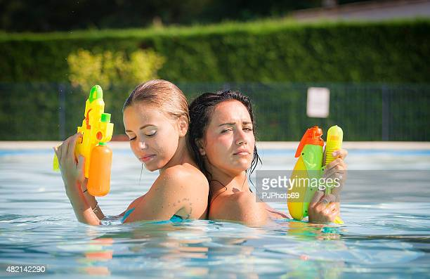 two young women having fun on swimming pool - pjphoto69 stock pictures, royalty-free photos & images