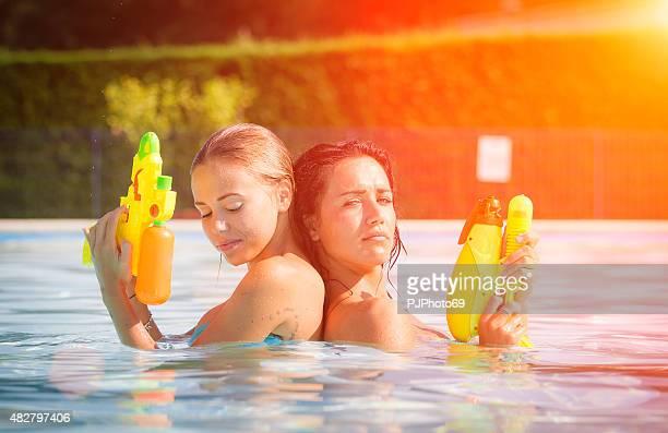 dos mujeres jóvenes divirtiéndose en la piscina - pjphoto69 fotografías e imágenes de stock