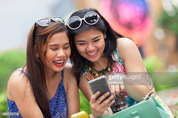 Two young women having fun using a smartphone
