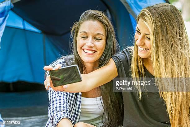 zwei junge frauen, die spaß mit smartphones - pjphoto69 stock-fotos und bilder