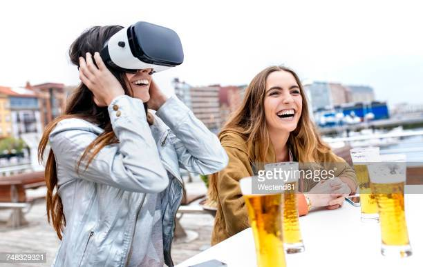 Two young women having fun with VR glasses in the city