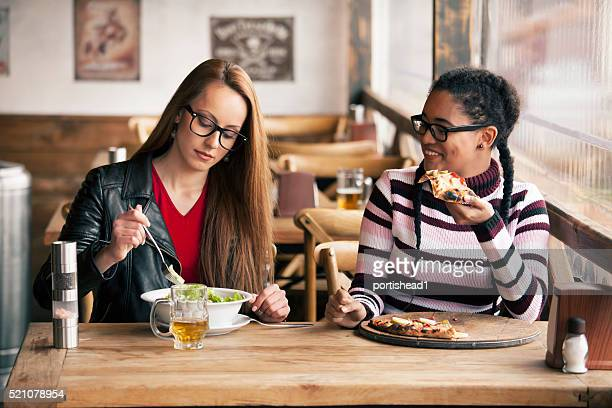 Two young women having lunch break at restaurant