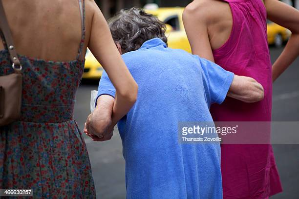 Two young women help their senior mother to cross the street in Athens, Greece