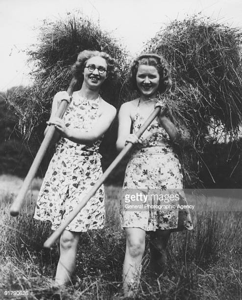 Two young women helping with the harvest on a farm in Ripley Surrey circa 1935