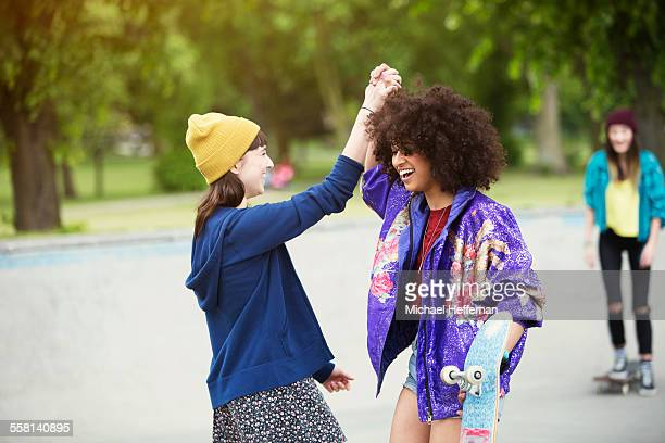 two young women high five at skate park - black hair stock pictures, royalty-free photos & images