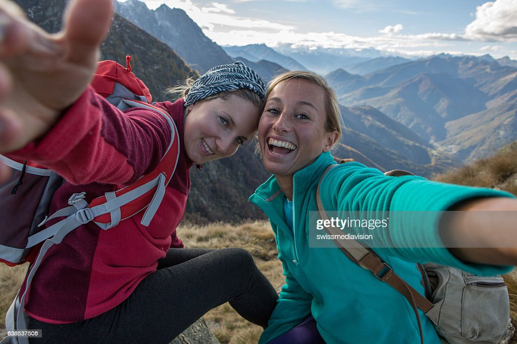 Two young women hiking take selfie portrait at mountain top : Stock Photo