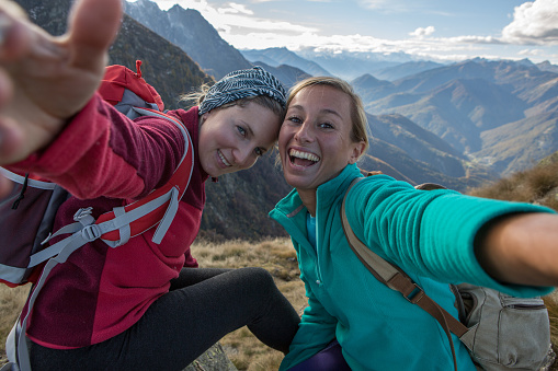 Two young women hiking take selfie portrait at mountain top - gettyimageskorea