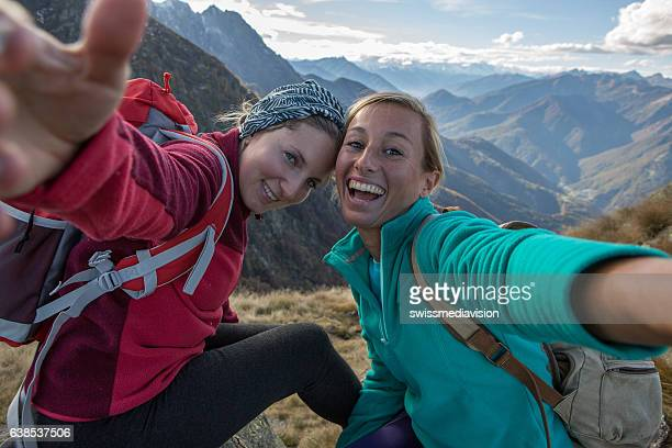 two young women hiking take selfie portrait at mountain top - young adult photos stock photos and pictures