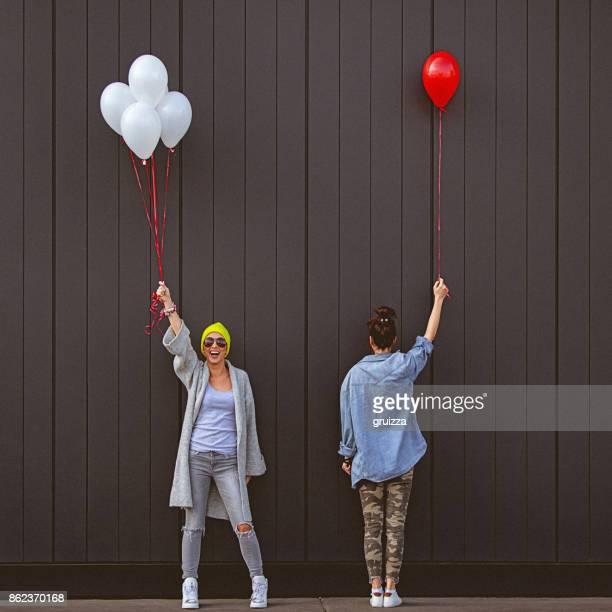 Deux jeunes femmes tenant des ballons en se tenant debout contre le mur gris