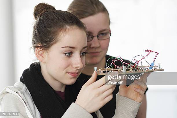 Two young women holding component an optical sensor in an electronic workshop