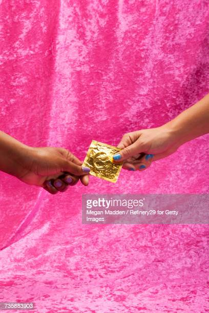 two young women holding condom - rubber stock pictures, royalty-free photos & images