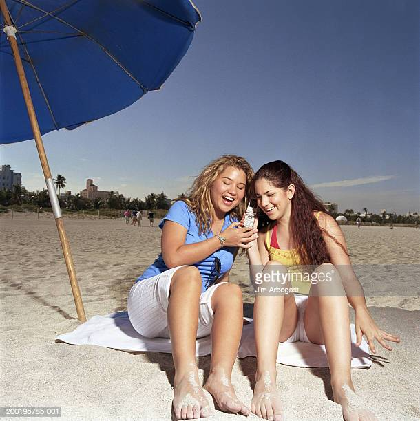 Two young women holding mobile phone, sitting on beach, smiling