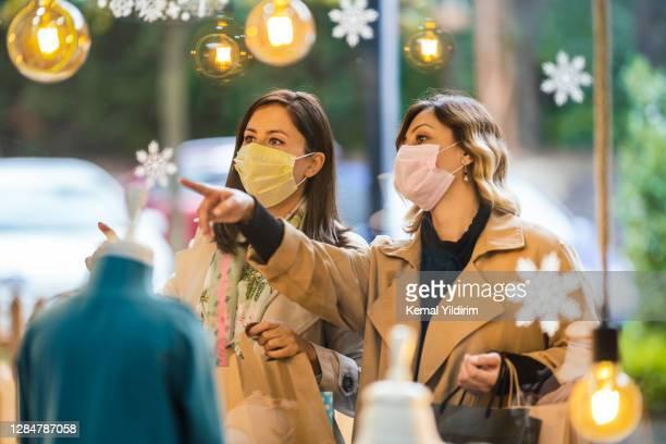 covid-19のために買い物袋を持ち、フェイスマスクを着用している2人の若い女性 - ギフトショップ ストックフォトと画像