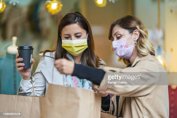 two young women holding shopping bags and wearing face mask because of covid-19 - middle east stock pictures, royalty-free photos & images