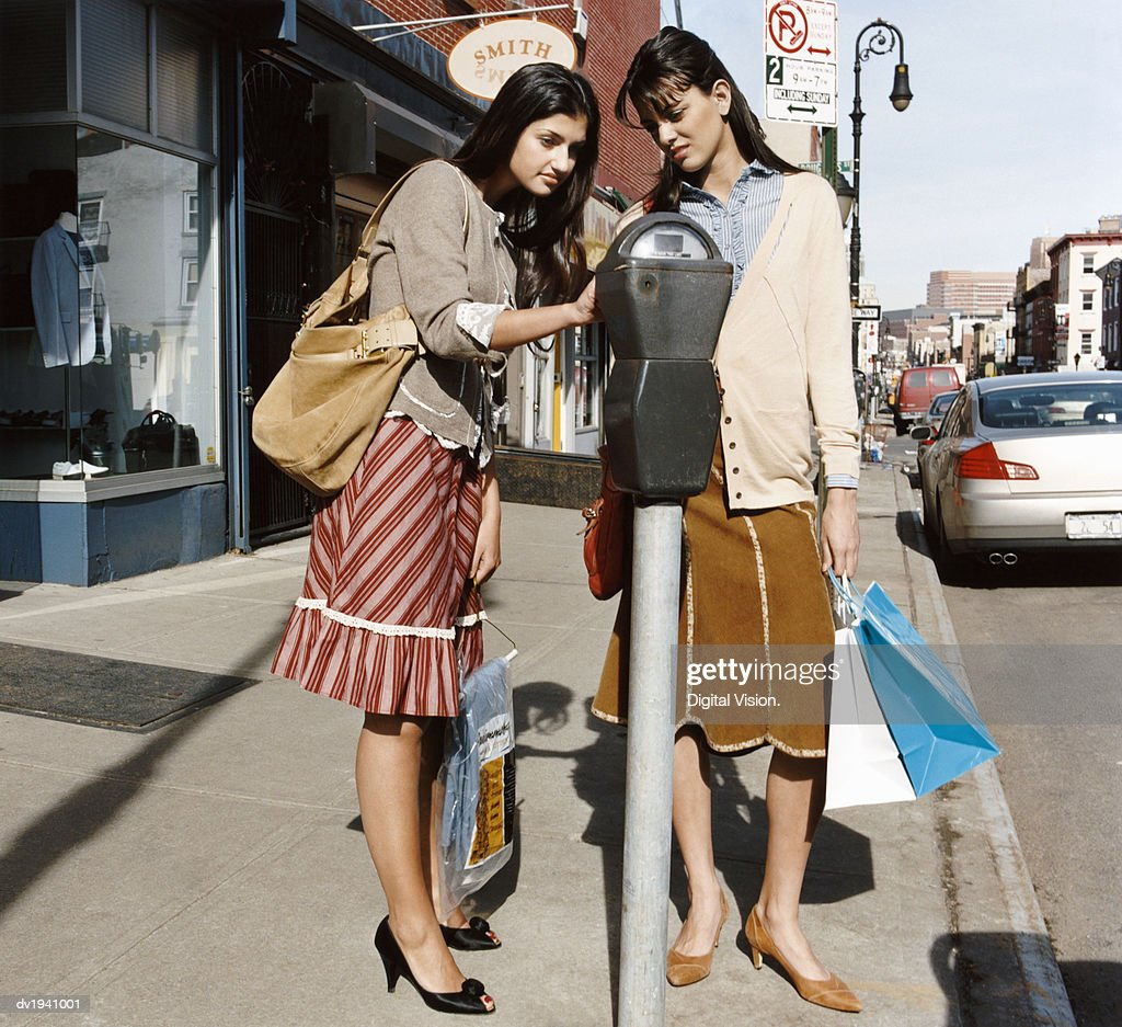 Two Young Women Holding Shopping Bags Operating a Parking Meter on a High Street : Stock Photo