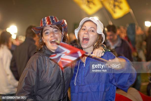 two young women holding union jack flag and singing, portrait - andrew jack stock pictures, royalty-free photos & images