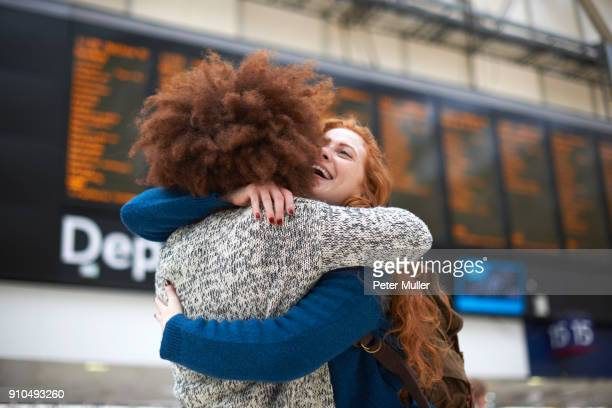 two young women hugging at train station - railway station stock pictures, royalty-free photos & images