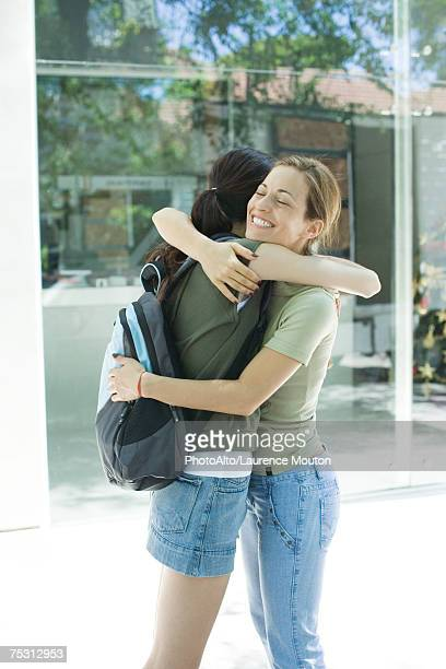 Two young women hugging each other, side view